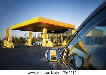 Car in gas station. Reflection on motor vehicle mirror and glass. Convenience store in Estonia - stock photo