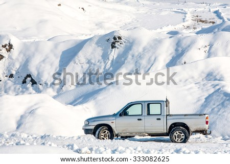 Car In Winter Scenario With Marks On The Road Suggesting Off Road Capabilities - stock photo