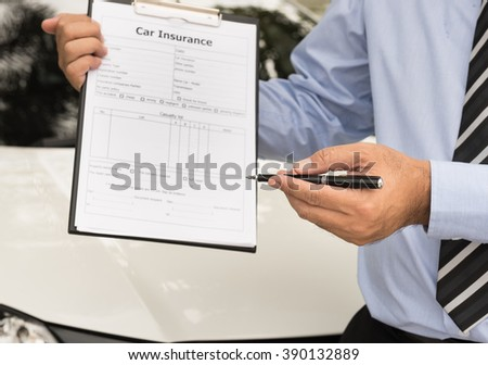 Car insurance agent send a pen to his customers sign the insurance form. - stock photo