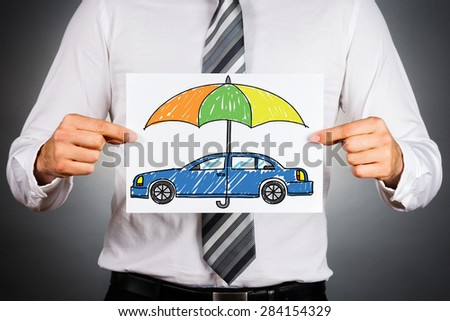Car insurance concept. Businessman holding white paper with drawn colorful car under safety umbrella. - stock photo