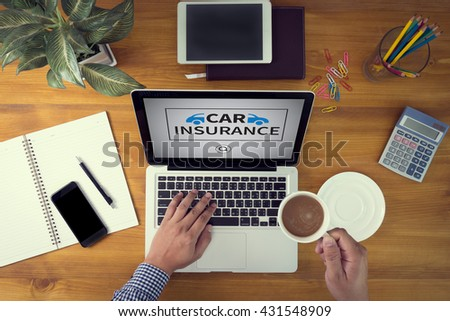 CAR INSURANCE Laptop and coffee cup in man work hands sitting on a wooden table - stock photo