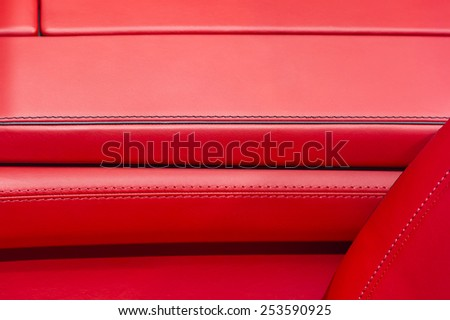 Car interior covered by genuine red high quality leather - luxury sport automobile - stock photo