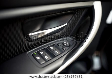 car interior details of door handle with windows controls and adjustments. Car window controls and details - stock photo