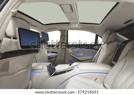 Car interior luxury. Interior of prestige modern car. Leather comfortable seats, multimedia & panoramic rooftop. White cockpit with exclusive wood & metal decoration on isolated white background. - stock photo