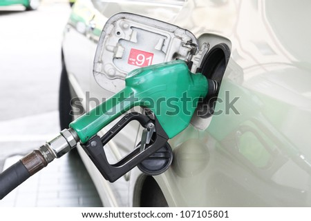 Car is filling gasoline at gas station - stock photo