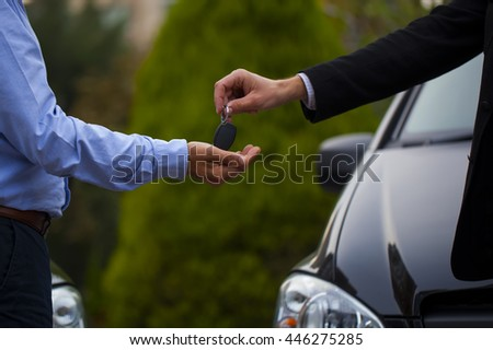 Car Key and Deal.man gives a car key to the other man