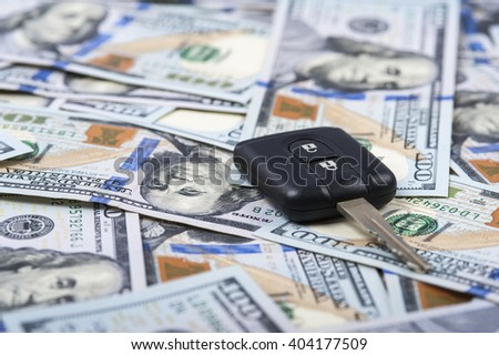 Car key and heap of one hundred dollar bills. Selective focus. - stock photo