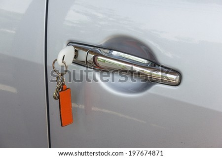 Car key and remote control insetered and hanging from door