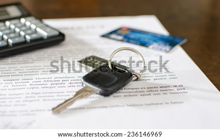 Car key, credit card on a signed sales contract, closeup - stock photo