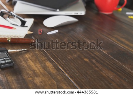 car key, digital tablet, laptop computer and notebook on wooden office desk