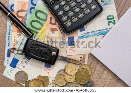 car key, euro banknotes, pen, coins and notebook