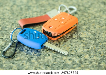 Car key in colorful silicone on polished stone  - stock photo