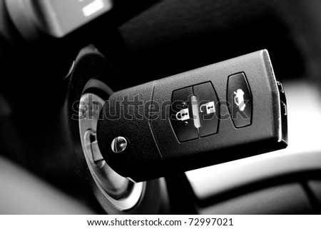 Car key into ignition lock, b&w - stock photo