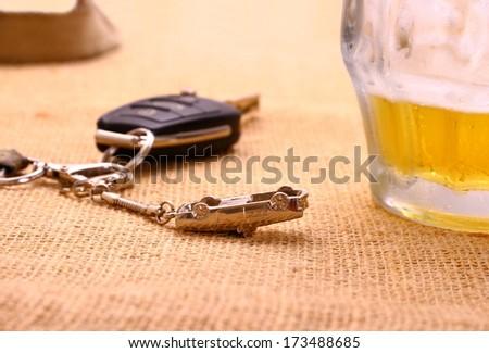 Car key with accident and beer mug, horizontal - stock photo