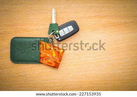 Car key with remote control and credit card on the wooden table surface - stock photo