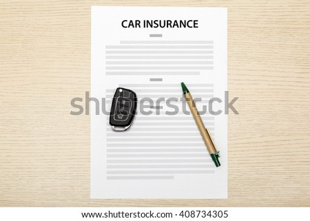 Car keys and pen laying on a blank of insurance. - stock photo