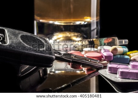 Car keys and pills isolated on black background with reflection
