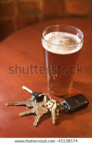 Car keys lying next to a full glass of beer.  Vertical shot. - stock photo