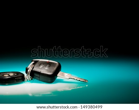 Car keys on blue, reflective table and black background - stock photo