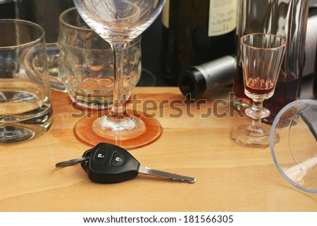 Car keys on the table full of empty glasses, bottles and spilled wine after a party, don't drink and drive concept - stock photo