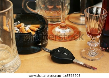 Car keys on the table full of empty glasses, bottles, full ashtray and spilled drink after a party, don't drink and drive concept - stock photo