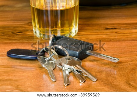 car keys with a glass of whiskey shallow dof focus on the keys - stock photo