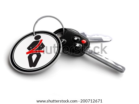 Car keys with key ring. Seat belt icon on keyring. Buckle up for safe driving and use you seat belt. - stock photo
