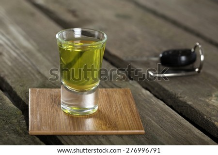 Car keys with one shot glasses over wood background - drink drive concept - stock photo