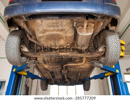 car lifted on repair stand in mechanic garage - stock photo
