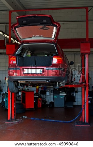 Car lifted up on the repair stand in garage - stock photo