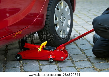 Car Lifted With Red Hydraulic Floor Jack For Repairing - stock photo