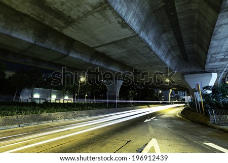 Car light trail under highway - stock photo