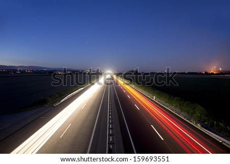 Car light trails at night on highway. - stock photo
