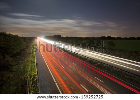 car light trails at night on motorway / highway - stock photo