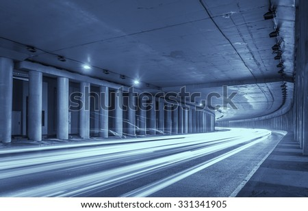 Car light trails in highway tunnel - stock photo