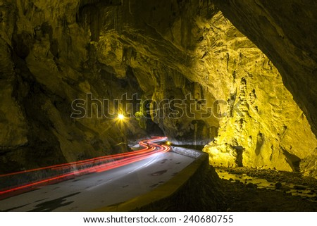 Car light trails into a cove. Art image . Long exposure photo taken in a natural cove with a river - stock photo