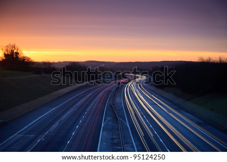 Car light trails on a motorway with sunrise in the distance - stock photo