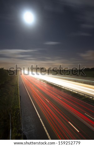 car light trails on motorway with moon - stock photo