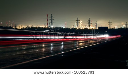 Car lights on a highway at night on the background of the industrial landscape. - stock photo