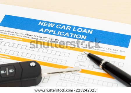 Car loan application with car key and pen - stock photo