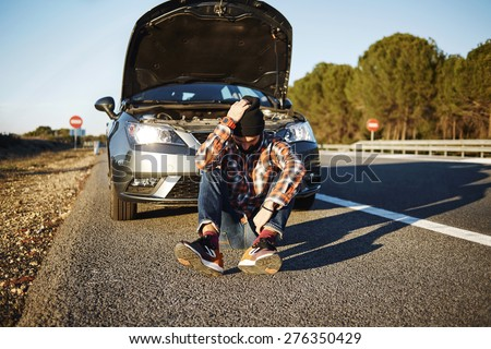 Car man sits near the broken automobile, sad and upset. Young man driver holding his head in freeway and thinks call a friend. Mixed race Caucasian male model sits during sunset and waiting help.  - stock photo