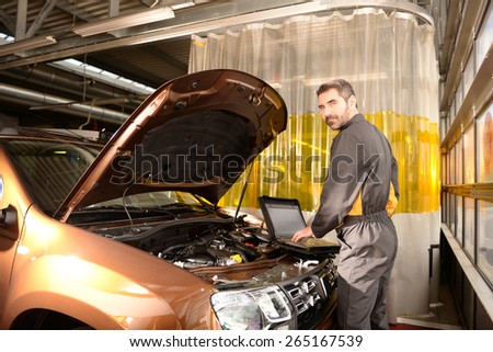 Car mechanic checking car at auto repair shop service station, computer control - stock photo