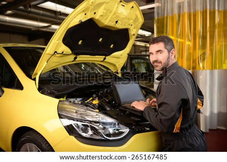 Car mechanic checking car at auto repair shop service station, motor management inspection with special computer unit - stock photo