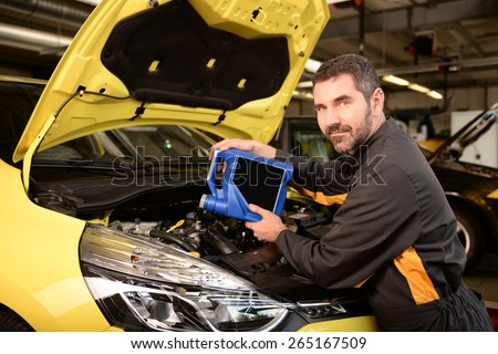 Car mechanic checking car at auto repair shop service station, oil inspection and refill - stock photo