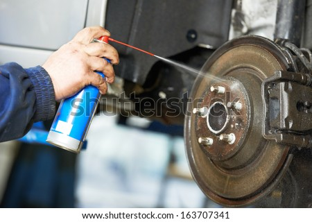 car mechanic cleaning car wheel brake disk from rust corrosion at automobile repair service station - stock photo