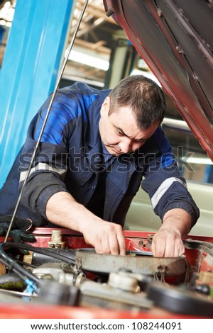car mechanic examining car engine of automobile at repair service station - stock photo