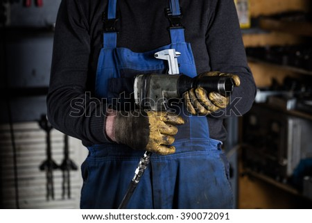 Car mechanic hands in garage with old gloves holds air impact wrench.  Concept - stock photo