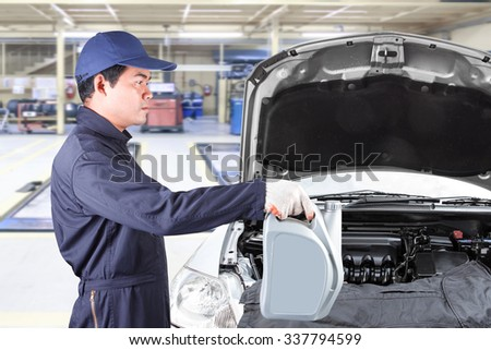 Car mechanic holding gray canister with engine oil for replacing and pouring oil into engine at maintenance repair service station  - stock photo