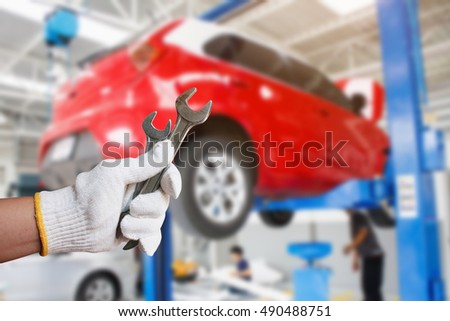 Car mechanic holding wrench at the car repair service garage
