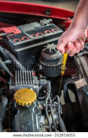 Car mechanic in auto repair service checking oil, red automobile
